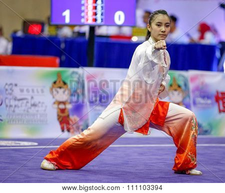JAKARTA, INDONESIA - NOVEMBER 16, 2015: Lu Yi Chan of Malaysia performs her movements in the Women's Compulsory Taijiquan event at the 13th World Wushu Championship 2015 at the Istora Senayan Stadium.