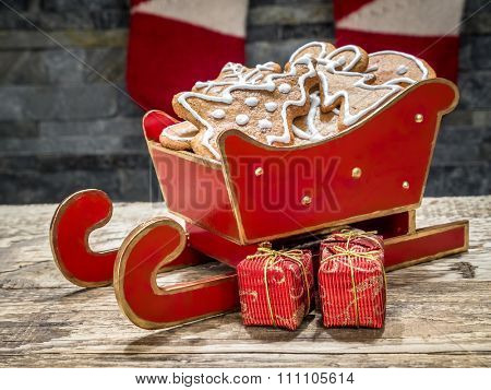 Assorted Christmas gingerbread cookies with white icing in red mini sleigh placed on table