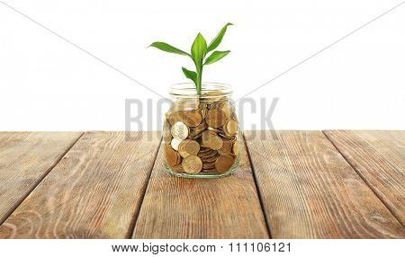Money and growing sprout in glass jar on wooden table
