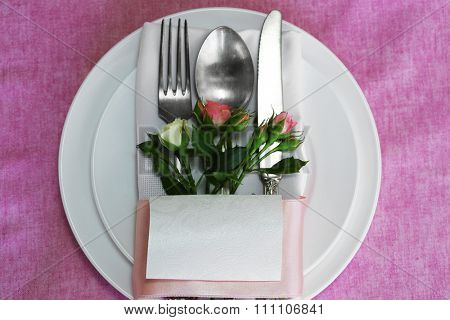 Cutlery and flowers for wedding party, on purple tablecloth background