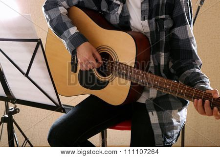 Musician plays guitar in light studio with musical notes holder, close up