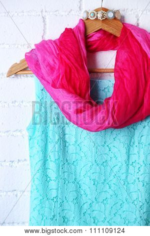 Dress, scarf and necklace on hanger on wall background