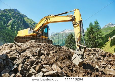 excavator loader machine during earthmoving works outdoors at mountain construction site