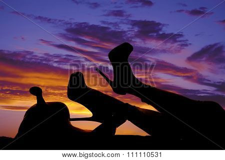 Silhouette Of Woman's Legs In Heels On Saddle In Sunset