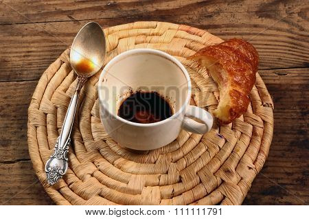 Empty Cup Of Coffee Teaspoon And Unfinished Croissant On Wicker
