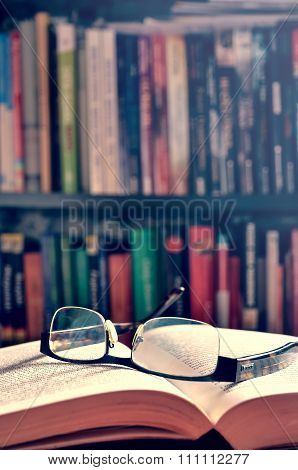 An open book and glasses.