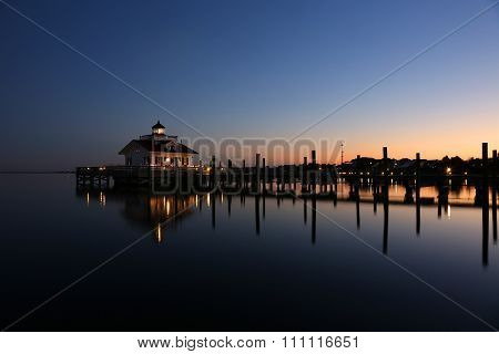 Lighthouse reflected in water at dusk
