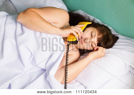 Woman Lying On Bed Talking On Landline Phone