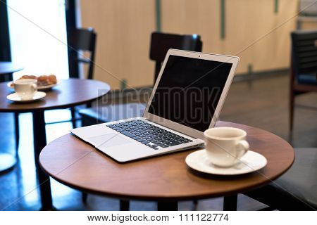 Laptop computer and coffee cup on wooden table