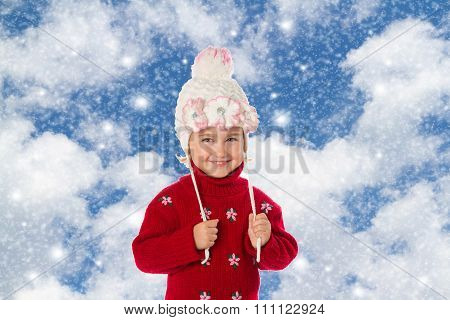 Little Girl With Ponytails In A Warm Hat And Red Sweater