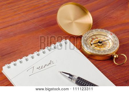 Notepad with handwritten word Trends and pen near compass on wooden board shallow depth of field