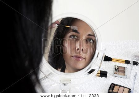 Woman sitting at a table, applying make-up in a small mirror