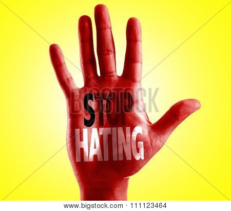 Stop Hating written on hand with yellow background