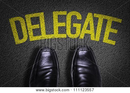 Top View of Business Shoes on the floor with the text: Delegate