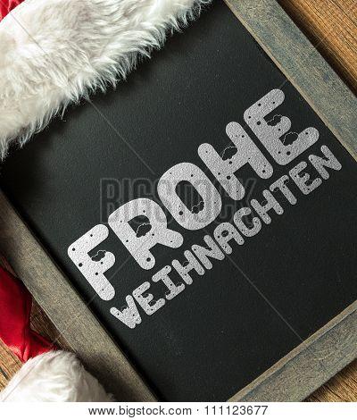 Merry Christmas (in German) written on blackboard with santa hat