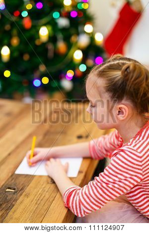 Adorable little girl writing letter to Santa in home beautifully decorated with Christmas tree and lights