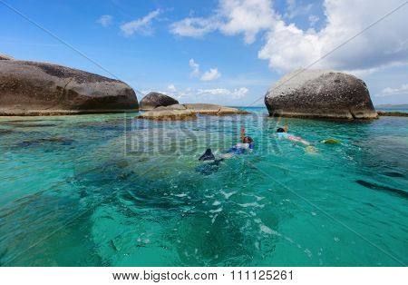 Family of young mother and son snorkeling in turquoise tropical water among huge granite boulders at beautiful tropical beach on Virgin Gorda,British Virgin Islands,Caribbean