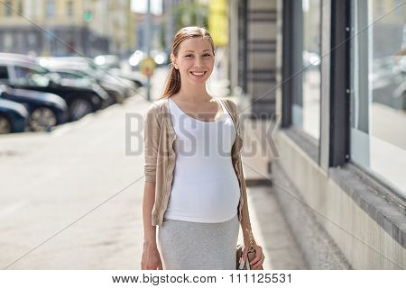 pregnancy, motherhood, people and expectation concept - happy smiling pregnant woman at city street