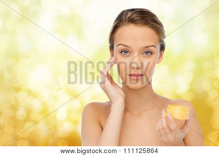 beauty, people, cosmetics, skincare and cosmetics concept - young woman appying cream to her face over yellow holidays lights background