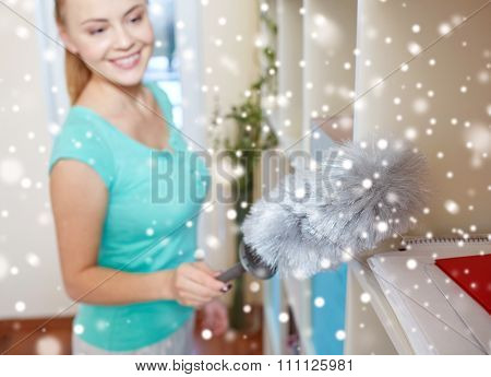 people, housework and housekeeping concept - happy woman with duster cleaning at home over snow effect