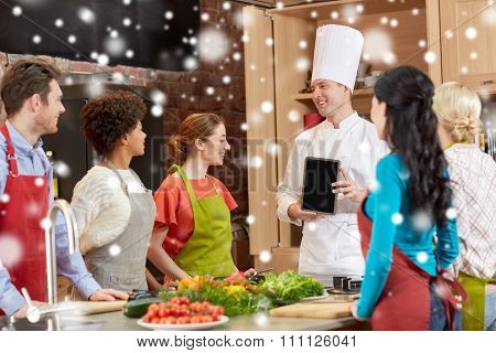 cooking class, culinary, food, technology and people concept - happy friends with chef cook showing blank tablet pc screen in kitchen over snow effect