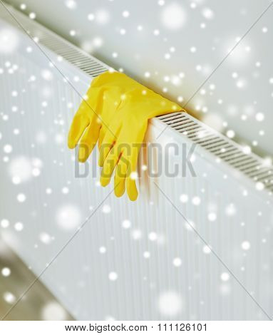 protection, housework and housekeeping concept - close up of yellow rubber gloves hanging on heater at home over snow effect