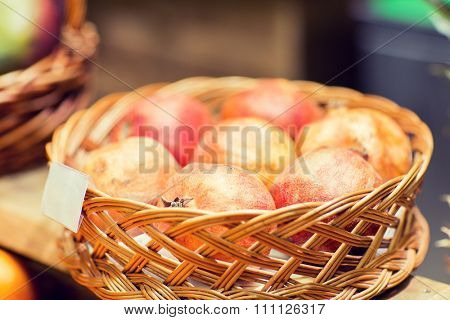sale, shopping and eco food concept - ripe pomegranates in basket with nameplate at grocery market