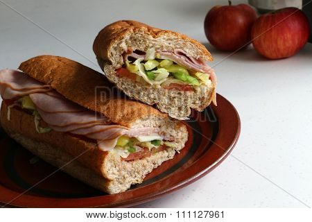Two halves of a submarine sandwich on brown plate with apples in background.