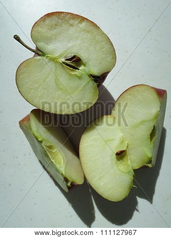 Apple cut in half, core exposed, with slices
