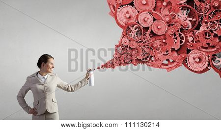 Young businesswoman spraying gear mechanism from aerosol balloon