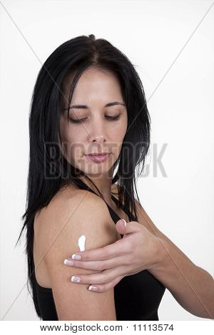 Woman applying moisturizing cream to her arm