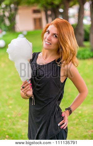 Smiling Girl In A Park Is Holding A Cotton Candy
