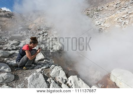 Young woman photographing smoking fumarole on crater active volcano. Kamchatka, Russia, Eurasia