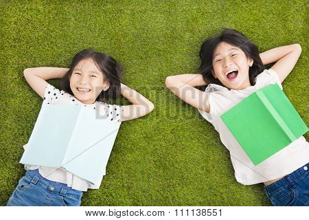 Happy Little  Girls With Book And Resting On The Grass