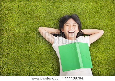 Happy Little  Girl With Book And Resting On The Grass