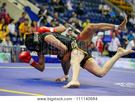 JAKARTA, INDONESIA - NOVEMBER 16, 2015: Caio Pitoli of Brazil (red) fights Youngkyu Ko of South Korea (black) in the men's 70kg Sanda event at the 13th World Wushu Championship 2015.