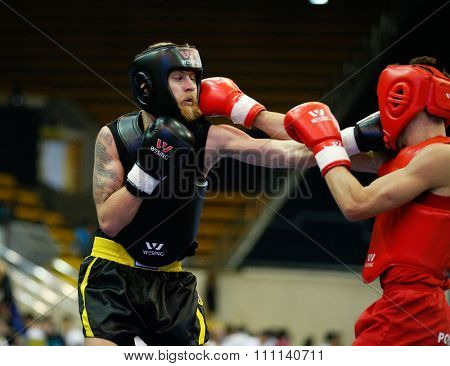 JAKARTA, INDONESIA - NOVEMBER 16, 2015: Francis Ferreira of Portugal (red) fights Thomas Raffetseder of Austria (black) in the men's 60kg Sanda event at the 13th World Wushu Championship 2015.