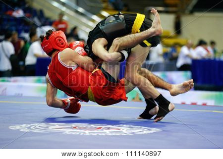 JAKARTA, INDONESIA - NOVEMBER 16, 2015: Ali Magomedov of Russia (red) fights Aliaksei Kaziuchyts of Belarus (black) in the men's 60kg Sanda event at the 13th World Wushu Championship 2015.