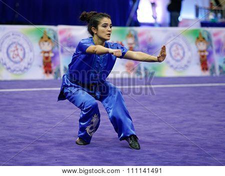 JAKARTA, INDONESIA - NOVEMBER 16, 2015: Sekour Dahbia of Algeria performs her movements in the Women's Compulsory Nanquan event at the 13th World Wushu Championship 2015 at the Istora Senayan Stadium.