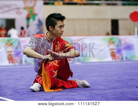 JAKARTA, INDONESIA - NOVEMBER 16, 2015: Dominic Chow of the USA performs the movements in the men's Daoshu event at the 13th World Wushu Championship 2015 at the Istora Senayan Stadium.