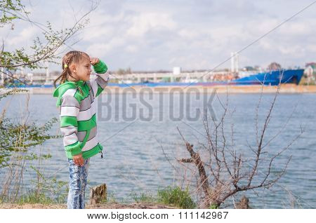 A Girl Stands Near The River On Which The Floating Ship And Looks Into The Distance