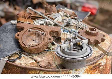 A Pile Of Old Broken Pieces Of Iron Lying On A Rusty Barrel