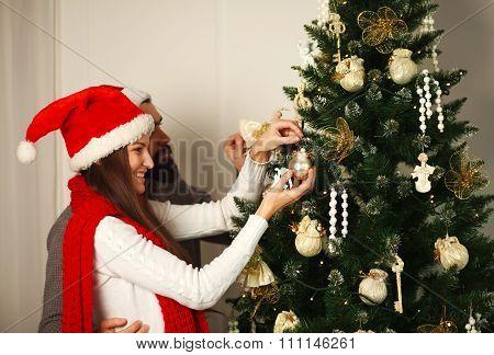 Joyful Couple In Red Hats Decorates Christmas Tree