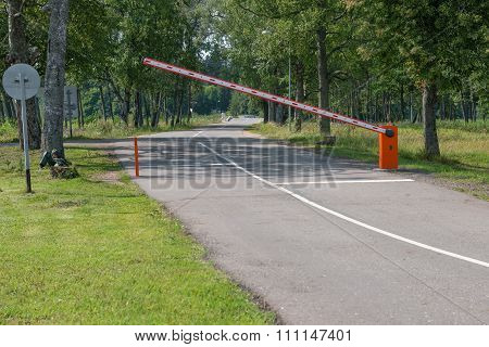 Rural Road In The Forest With Closed Red White Barrier