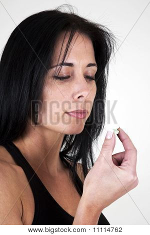 Woman putting tablet in her mouth