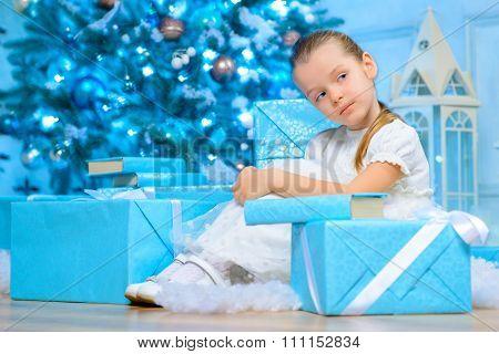 Little girl resting near Christmas tree