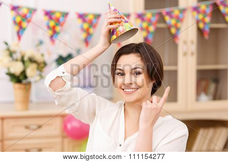 Young smiling girl tries on her party hat