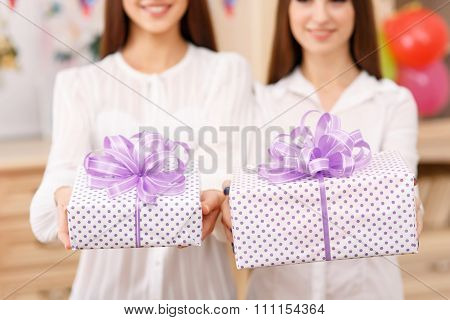 Two young ladies holding presents.