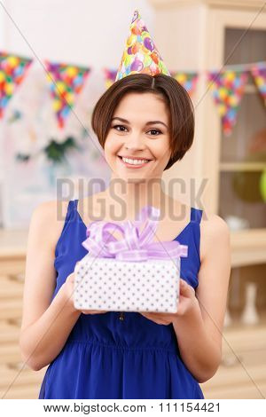 Happy young girl holding wrapped birthday gift.