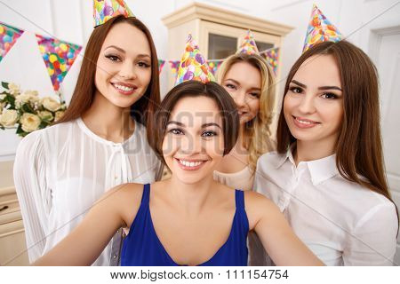 Attractive young girls making collective birthday selfie.